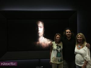 Matthew Penn frente a una de sus obras expuestas en el Palau Robert de Barcelona con Isabel y Manu Núñez